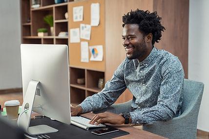 happy-african-businessman-using-computer-HYFSMPN.jpg