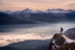 Man hiker looking landscape with fog sta