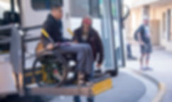 a volunteer helps a disabled veteran board a bus during the National Disabled Veterans Winter Sports Clinic adaptive sports program