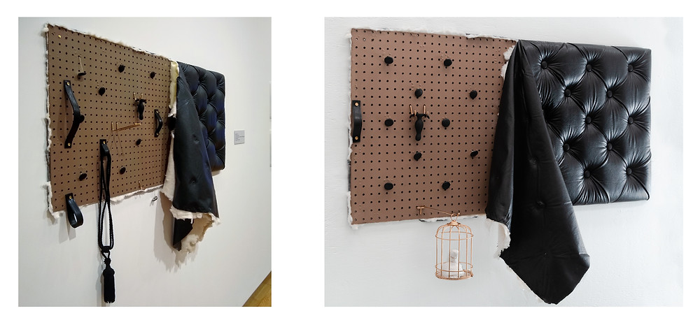 A black leather upholstered sculpture on a wall. The object is rectangular and diamond-tufted with five rows of diagonal buttons. Half of the piece is stripped off revealing a peg-board underneath in which various objects are attached using brass hardware including: tassels, sex toys, leather straps and handles, and a plaster penis in a gilded cage.