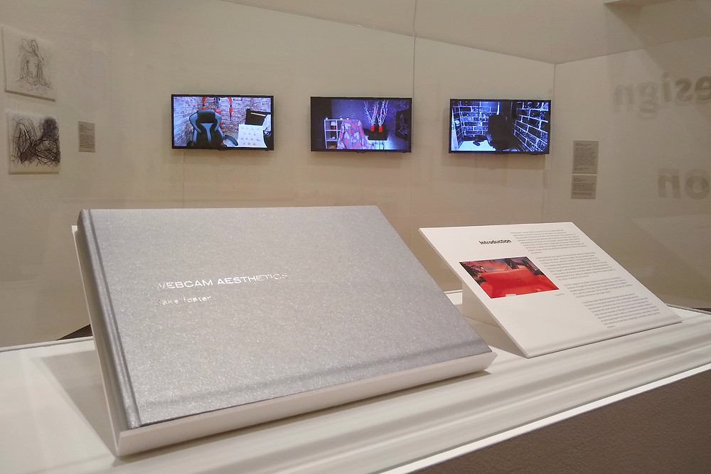 """A sparkly silver hard-cover book with a silver-stamped title reading """"Webcam Aesthetics: Jake Foster"""" is in a glass case next to a sample page. Beyond through the glass, three digital TV screens are visible depicting empty rooms."""