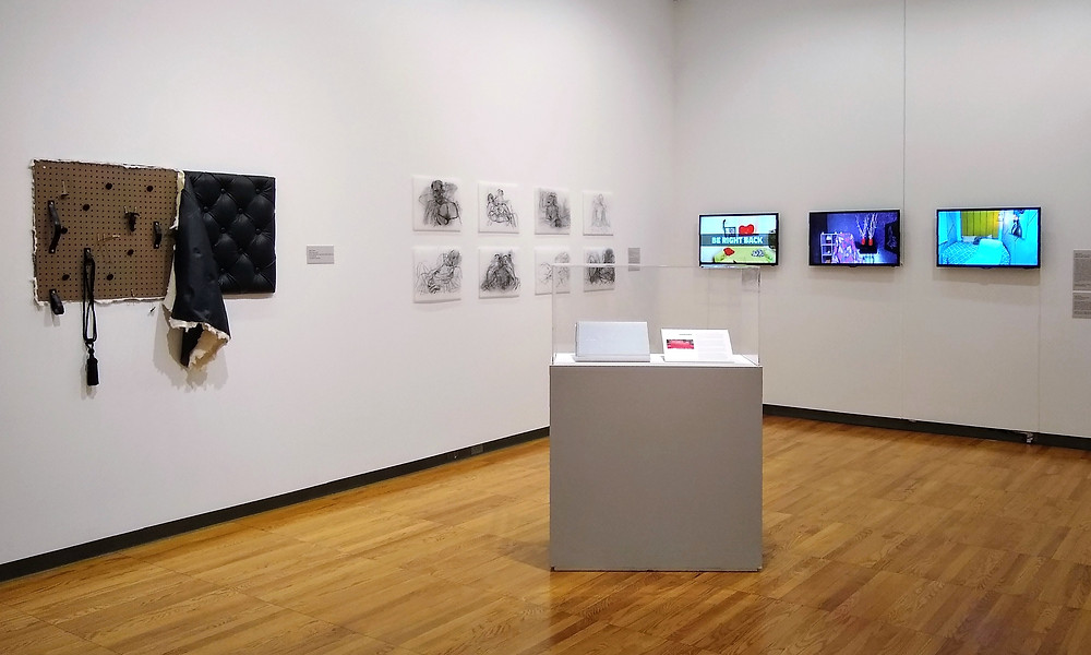 An image of artwork taken from afar in a white-walled museum setting. First to the left is an upholstered sculpture on a wall with black leather and sex toys. Then there are a series of 8 small, figurative, black and white drawings hung in two rows. A pedestal with a glass cover and a book sits in the center of the space, with three tv screens depicting empty rooms in the distance.