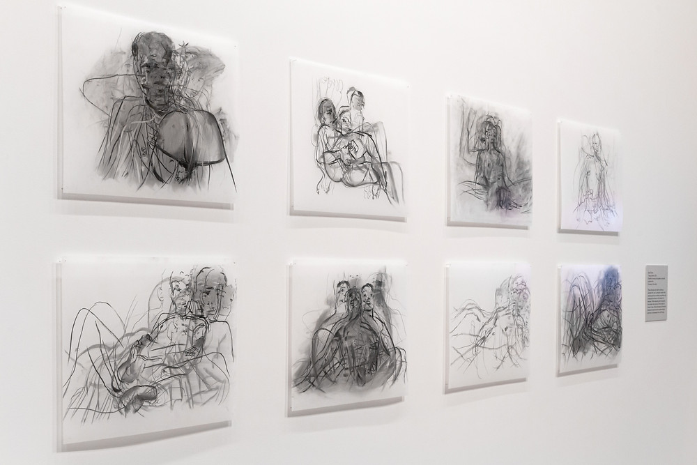 Eight small grey-scale drawings are hanging without frames on thin pins away from the wall. The work is linear, some more dense than others, and depicts abstracted erotic male figures.
