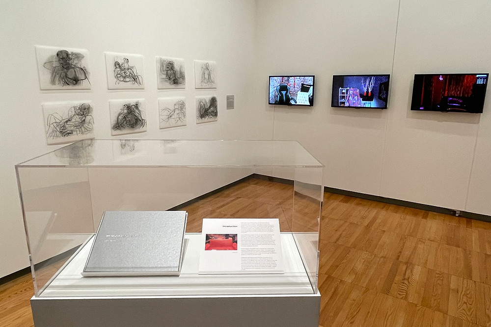 An image of artwork taken from afar in a white-walled museum setting. First to the left is a series of 8 small, figurative, black and white drawings hung in two rows. In the foreground, a pedestal with a glass cover and a book sits in the center of the space, with three tv screens depicting empty rooms in the distance.