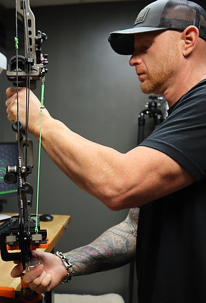 A member of the Rad Archery team, fixing a compound bow at the shop.