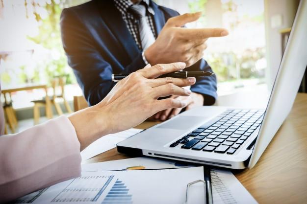 Na foto vemos em close up dois executivos, de terno, discutindo algo em uma reunião. Um computador aberto enquanto um e-mail é redigido.