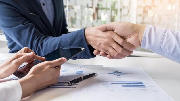 Empresários fechando acordo dando aperto de mãos