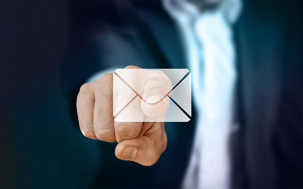 Imagem de um homem com terno e gravata apontando com o dedo indicador um holograma com o símbolo de e-mail na forma de um enveope