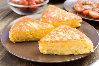 potato-tortilla-pieces-in-clay-dish-on-w