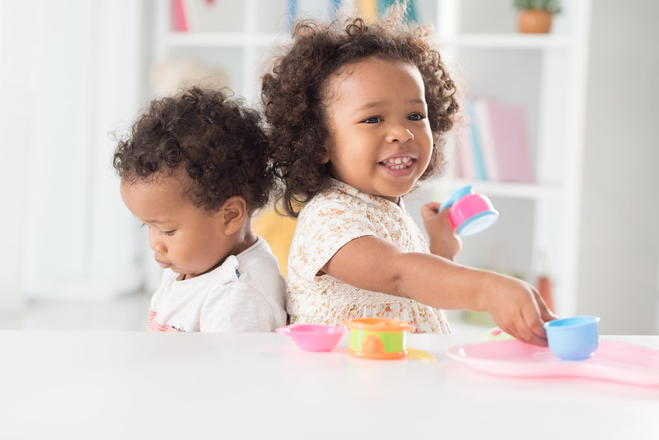 Image of little girl and boy playing with tea set