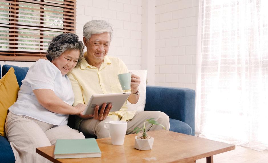 asian-elderly-couple-using-tablet-drinki