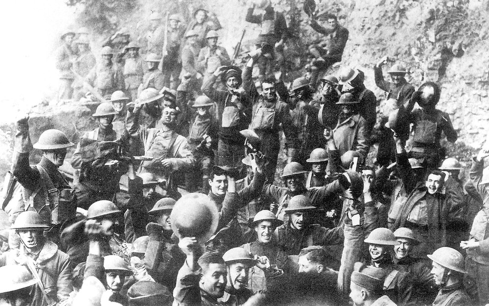 Men of US 64th Regiment, 7th Infantry Division, celebrate the news of the Armistice, 11 November 1918, Public Domain.