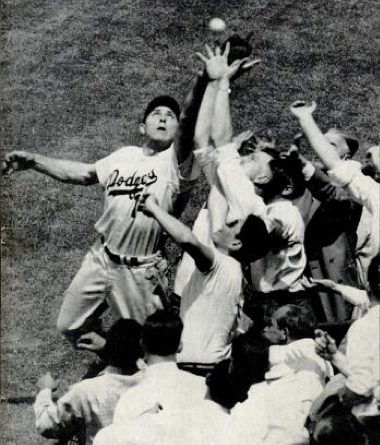 Gil Hodges attempting a catch at Ebbetts Field. Back cover of Baseball Digest March 1953. Public Domain.