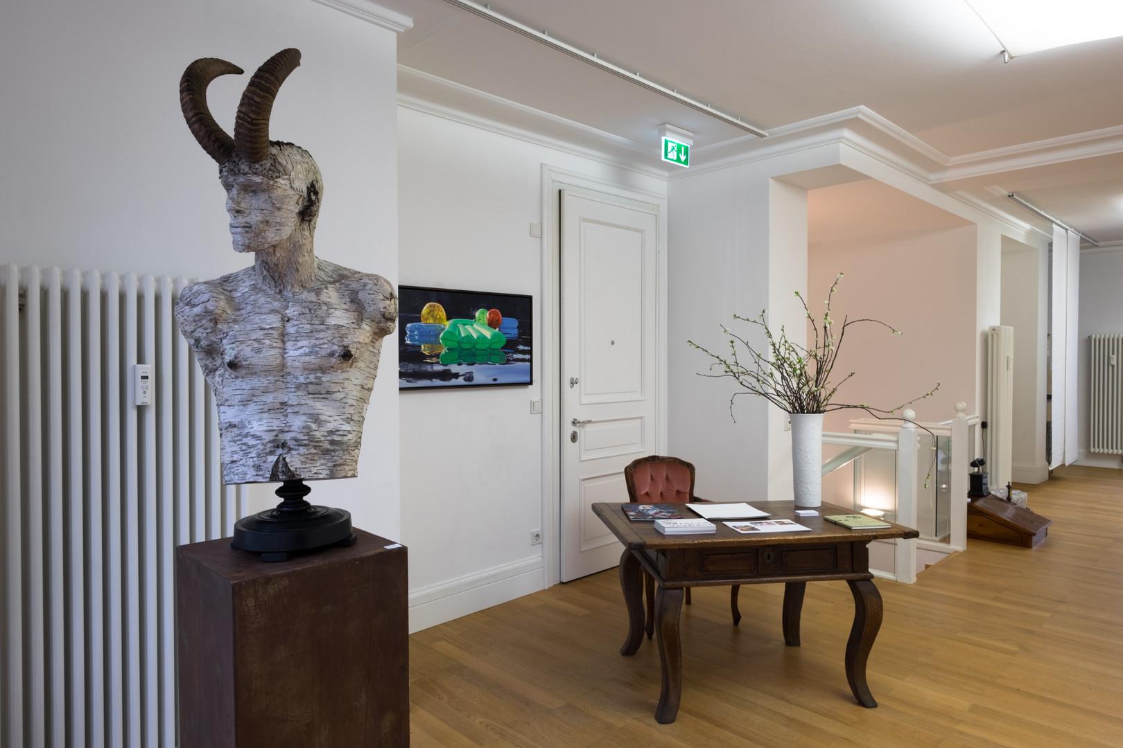 """Ausstellungsansicht """"Szenenwechsel"""": Holzskulptur Waldgott von Friedrich Schreiber, green lilo von Cameron Rudd"""