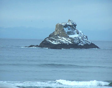 Snow covered Castle Rock off the Arch Cape coastline