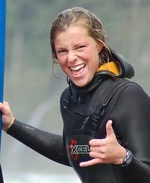 Lauren Ahlgrn in wetsuit holding a surf board