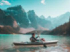 Man padling a grey kayack thru a high mountain lake