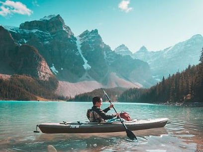 Man padling a grey kayack thru a high mountain lake