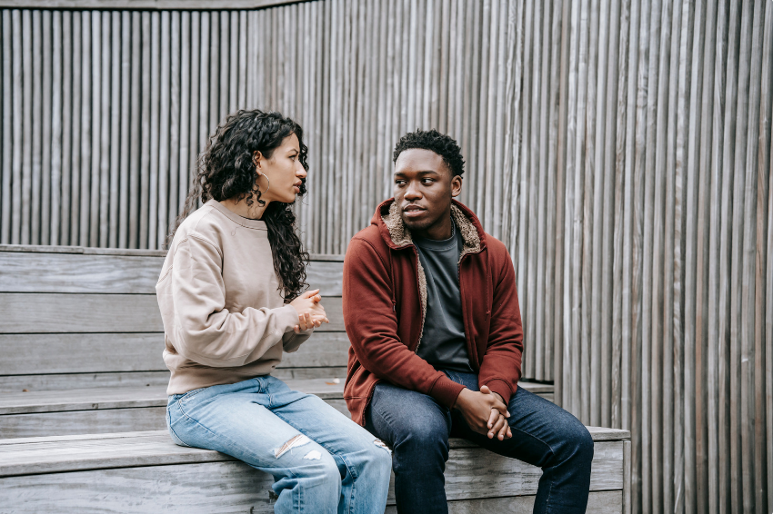 A woman and a man in their late teens or 20s sitting on a wooden bench. The woman is gesturing as the man listens.