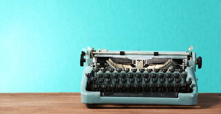 Old retro typewriter on table on green b