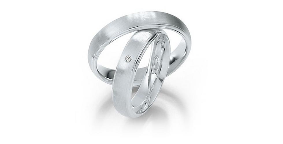 Lekerekített szélű, domború felületű fehérarany jegygyűrűpár középen gyémánttal