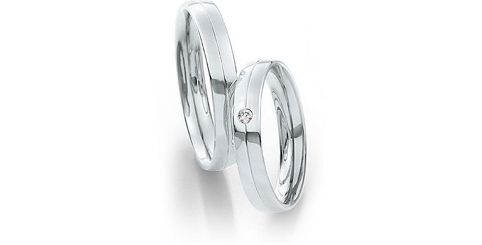 Lekerekített szélű fehérarany jegygyűrű középen véséssel és gyémánttal