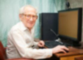 smiling happy old man sitting near compu