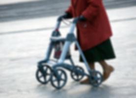 An elderly woman walking on the street w