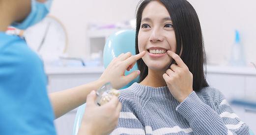 Woman talk to dentist in dental clinic .