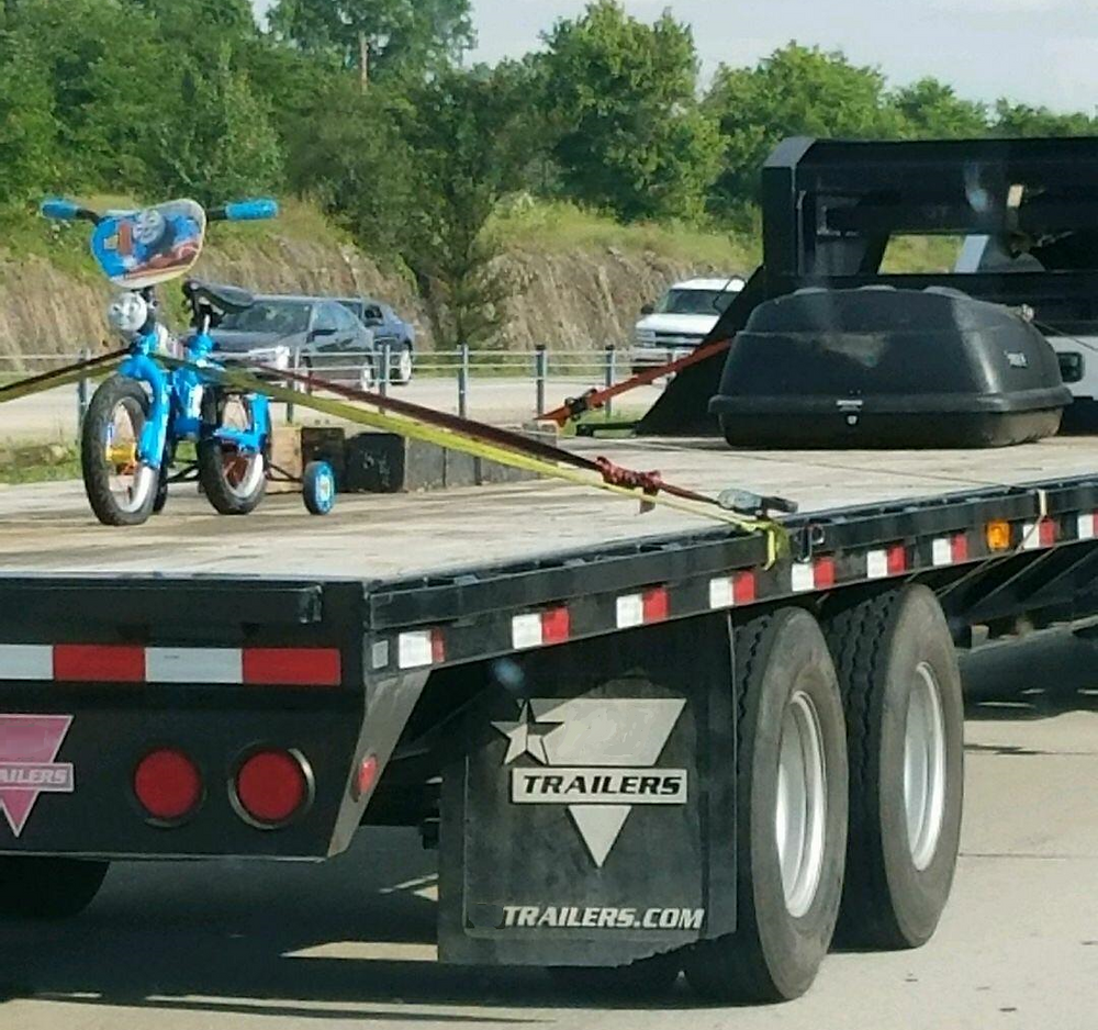 A large flat-bed trailer truck carrying a single child's bicycle