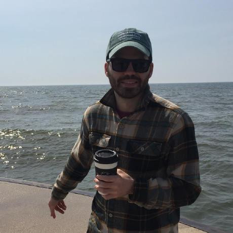 A picture of James Bourbeau in front of a body of water holding a cup of coffee and wearing sunglasses