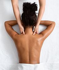 Female therapist massaging black woman n