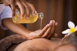 Closeup of masseur hands pouring aroma o