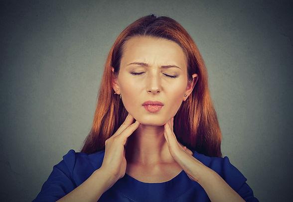 Closeup girl with sore throat touching h