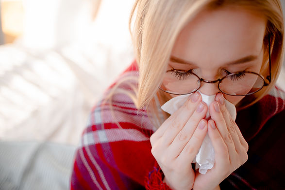 Blond woman having cold and blocked nose