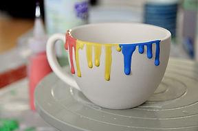 Cappucino-Tasse, an deren Rand Farbe langsam nach unten tropft.
