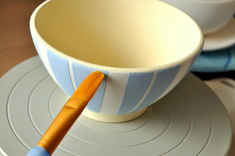 Schale aus Keramik wird mit Streifen bemalt.