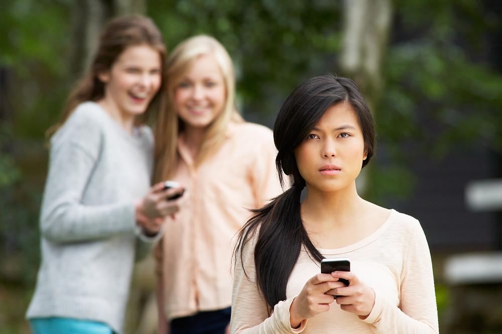 Teenage girls bullying another girl on social media.