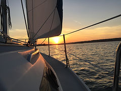 Sunset off the bow of sailboat