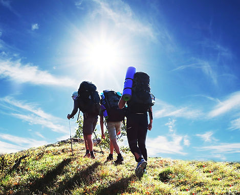 Group of young backpackers ascend grassy peak under bright sun and blue skies