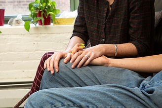 A couple holding hands on a couch.jpg