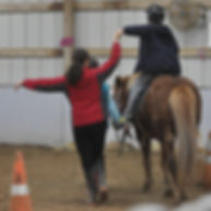 instructor helping rider on horseback
