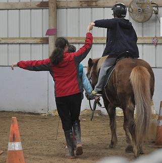 instructor helping rider on horseback