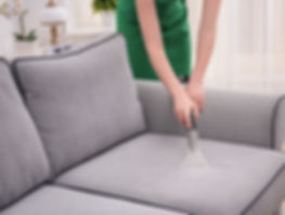 Woman-cleaning-couch-with-vacu-211557541