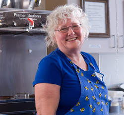 Board Member Susan Heyer working in the kitchen