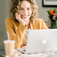 Black and white image of woman sitting at a laptop resting her face on her hand