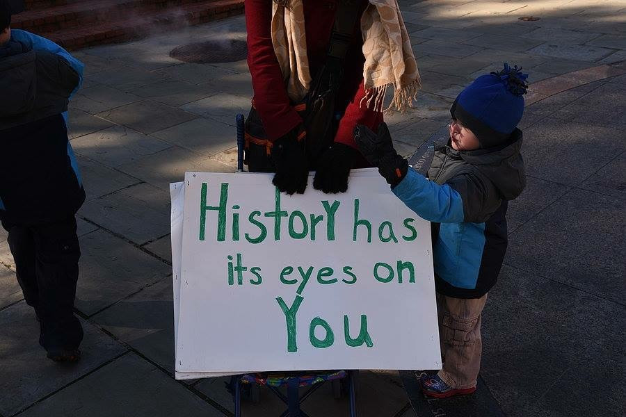 """Woman holding a protest sign that says """"History has its eyes on you"""" and a young child."""