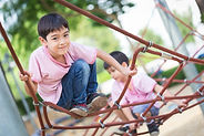 Little asian boy climbing rope obstacle