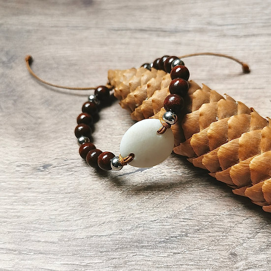 Bracelet ajustable avec perles en bois marron, au centre une pierre plate blanche