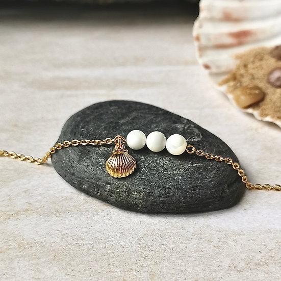 Bracelet doré avec au centre 3 perles en nacres et un pendentif coquillage